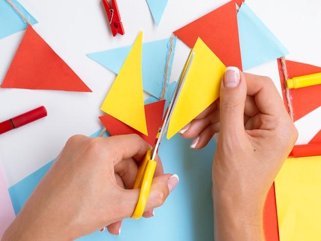 Vista superior de mujer cortando papel colorido