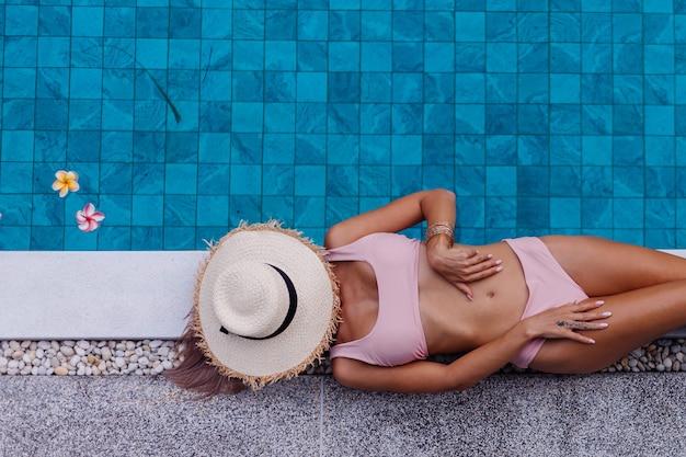 Vista superior de la mujer delgada en bikini en el borde de la piscina disfrutando de las vacaciones
