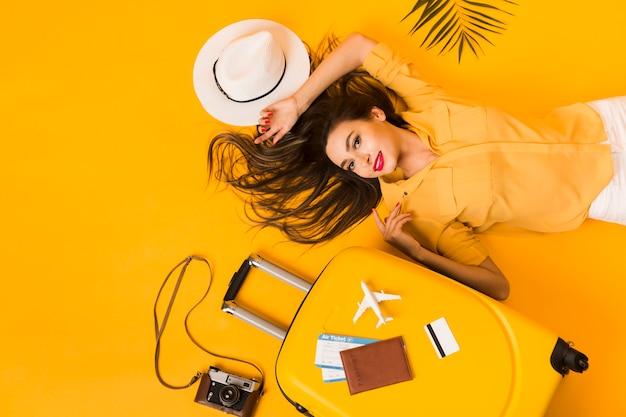 Vista superior de mujer con elementos esenciales de viaje