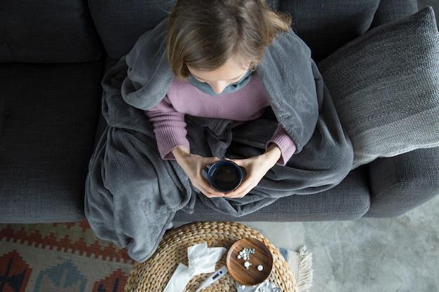 Vista superior de una mujer enferma en casa, sosteniendo una taza verde en las manos