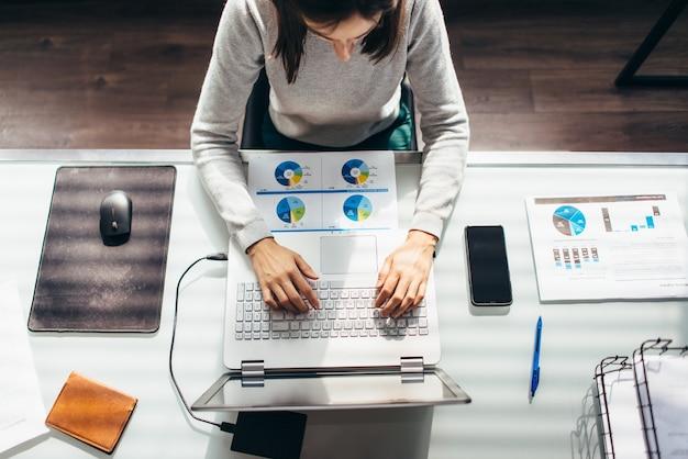 Vista superior de la mujer escribiendo en la computadora portátil, trabajando desde casa.