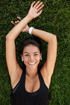 Vista superior de una mujer feliz fitness en colocación de auriculares