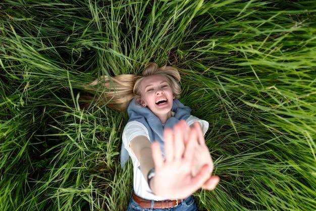 Vista superior de mujer feliz posando en pasto