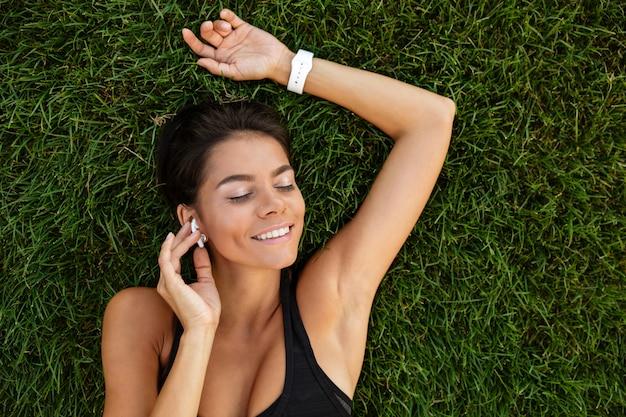 Vista superior de una mujer de gimnasio satisfecho en colocación de auriculares