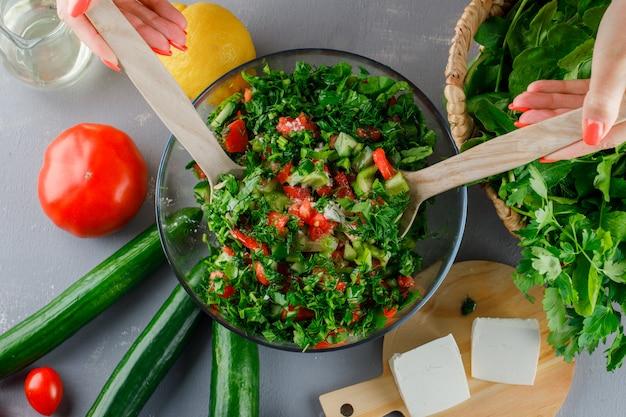 Vista superior mujer haciendo ensalada de verduras en un recipiente de vidrio con tomates, queso, verduras, pepino en superficie gris