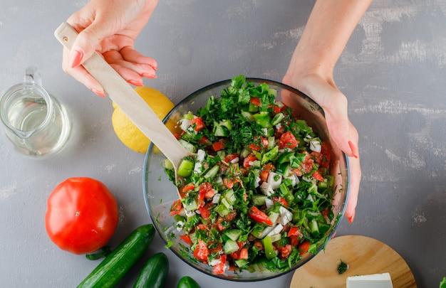 Vista superior mujer haciendo ensalada de verduras en un tazón de vidrio con tomate, pepino, limón sobre superficie gris