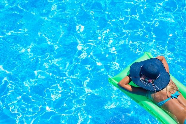 Vista superior de la mujer joven delgada en bikini en el colchón de aire verde en la piscina