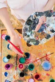 Vista superior mujer joven con elementos de pintura