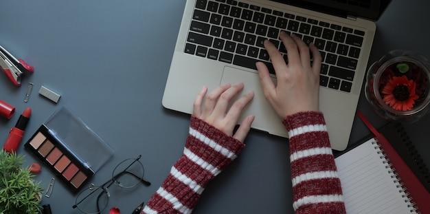 Vista superior de una mujer joven escribiendo en la computadora portátil en el espacio de trabajo femenino de lujo rojo
