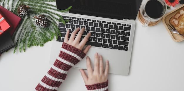 Vista superior de una mujer joven escribiendo en la computadora portátil en navidad decorado lugar de trabajo