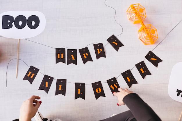 Vista superior de una mujer joven hace guirnalda de halloween. bricolaje creativo. fiesta de proyecto de decoración del hogar. inspiración de manualidades de halloween.