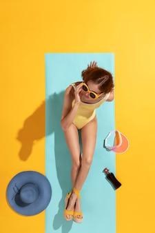 Vista superior, mujer joven, posar, en, traje de baño