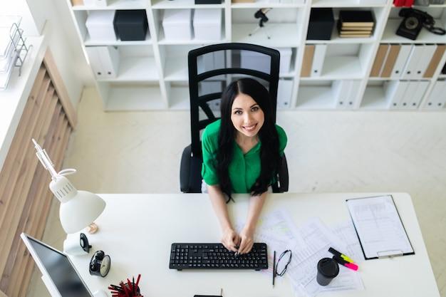 Vista superior de una mujer joven sentada en un escritorio de oficina y escribiendo en un teclado.