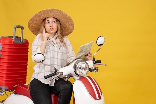 Vista superior de una mujer joven con sombrero y sentada en una motocicleta y sosteniendo el mapa apuntando hacia arriba en amarillo