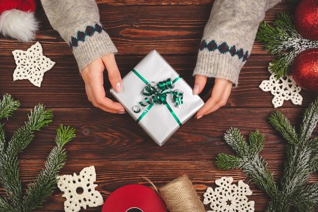Vista superior de una mujer manos con un regalo de navidad en madera