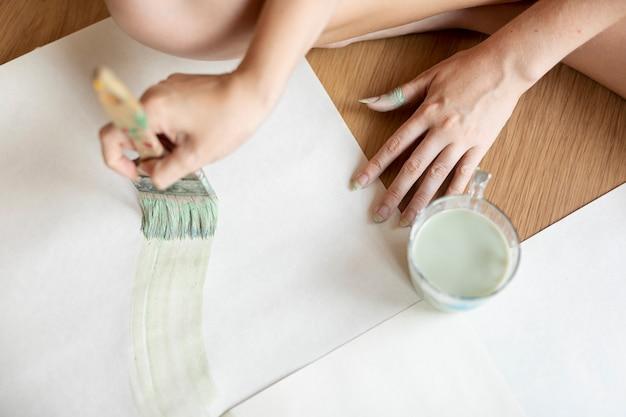 Vista superior mujer pintando en el piso