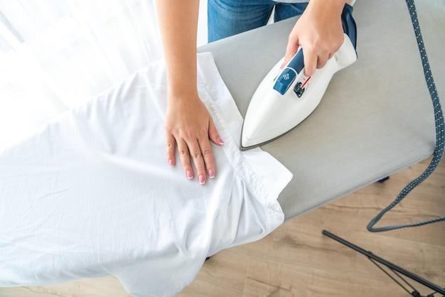 Vista superior de la mujer planchar cuello de camisa blanca en tabla de planchar