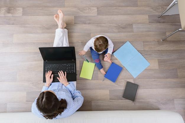 Vista superior de la mujer con el portátil con el niño sentado en el suelo