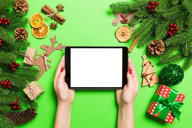 Vista superior de la mujer que sostiene la tableta en sus manos sobre fondo verde