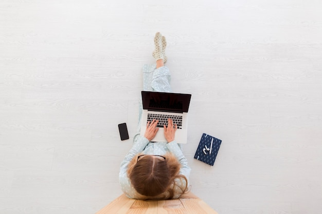 Vista superior de la mujer que trabaja desde su casa en la computadora portátil en pijama