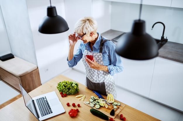 Vista superior de mujer senior en delantal de pie en la cocina, bebiendo vino y mirando portátil