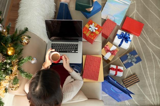 Vista superior de la mujer sentada en el sofá con laptop y café rodeada de numerosas cajas de regalo