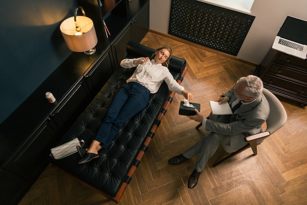 Vista superior de una mujer seria acostada en el sofá mientras habla de sus problemas psicológicos con su psicoterapeuta masculino