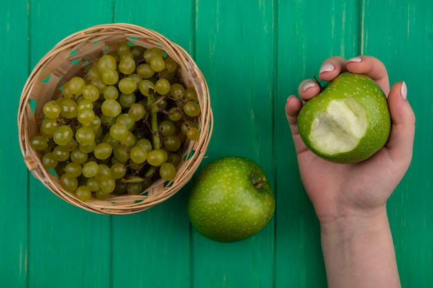 Vista superior mujer sosteniendo manzanas verdes una con uvas verdes y mordidas en canasta sobre fondo verde