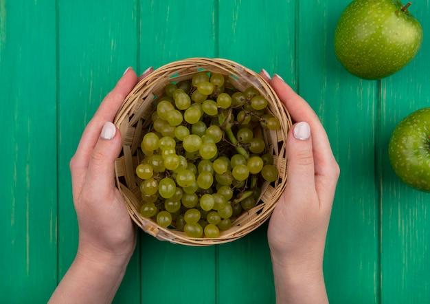 Vista superior mujer sosteniendo uvas verdes en una canasta con manzanas verdes sobre un fondo verde