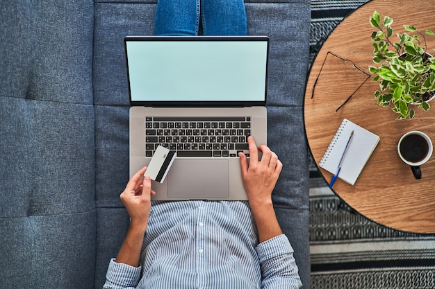 Vista superior de una mujer con una tarjeta de crédito y compras en línea en una computadora.