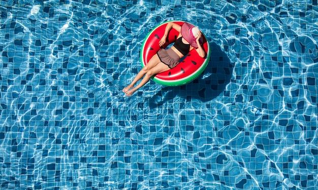 Vista superior de la mujer yacía en globo en el fondo de la piscina