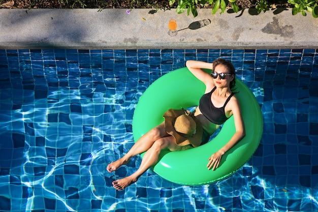 Vista superior de la mujer yacía en globo en la piscina
