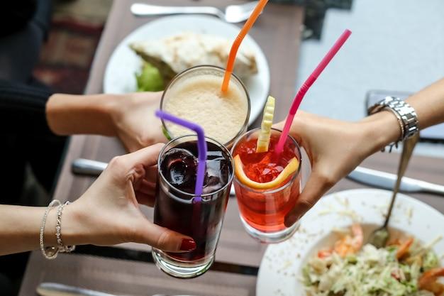 Vista superior mujeres bebiendo refrescos cola jugo de naranja fresco y limonada con pajitas de colores