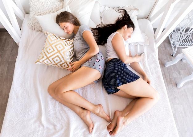 Vista superior mujeres durmiendo espalda con espalda