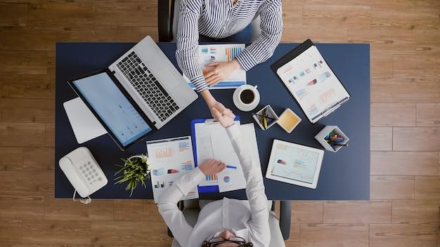 Vista superior de mujeres empresarias dándose la mano antes de analizar el papeleo de estadísticas de gestión