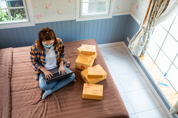 Vista superior las mujeres jóvenes de compras en línea comienzan una pequeña empresa en una caja de cartón en el trabajo.
