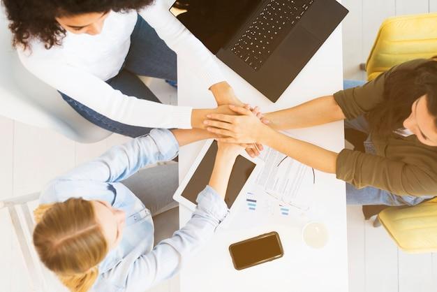 Vista superior mujeres de negocios dándose la mano