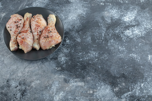 Vista superior de muslos de pollo crudo marinado sobre fondo gris.