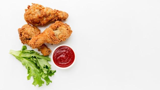 Vista superior de muslos de pollo frito con salsa de tomate y espacio de copia