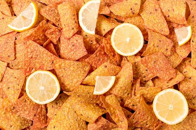 Vista superior de nacho chips con rodajas de limón