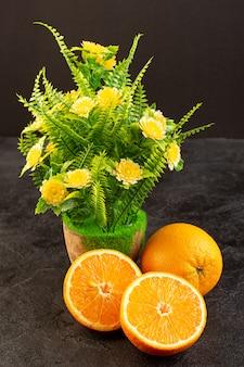 Una vista superior naranjas frescas agrias maduras enteras y en rodajas cítricos suaves vitamina amarilla amarilla en el oscuro escritorio