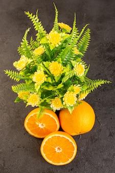 Una vista superior naranjas frescas agrias plantas maduras enteras y en rodajas cítricos suaves vitamina amarilla tropical en el oscuro escritorio