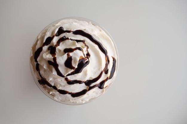 Vista superior de la nata montada con jarabe de chocolate en blanco