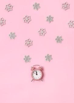 Vista superior de navidad año nuevo plano pone rosa despertador con copos de nieve copia espacio de fondo.