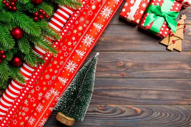 Vista superior de navidad hecha de abeto, papel de regalo enrollado y otras decoraciones en madera.
