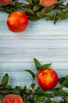 Vista superior de nectarinas maduras frescas con hojas verdes sobre fondo rústico de madera con espacio de copia