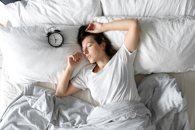Vista superior de una niña durmiendo junto a un reloj despertador. hora de despertar. en el reloj despertador 7 am sueño profundo.