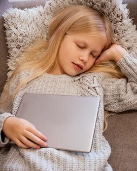 Vista superior de la niña durmiendo con tableta
