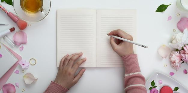 Vista superior de la niña escribiendo en el cuaderno en blanco en el dulce espacio de trabajo femenino rosa con maquillaje