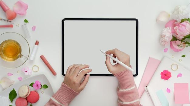 Vista superior de la niña escribiendo en la tableta de la pantalla en blanco en el espacio de trabajo femenino rosa dulce